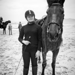 A young rider standing next to her horse