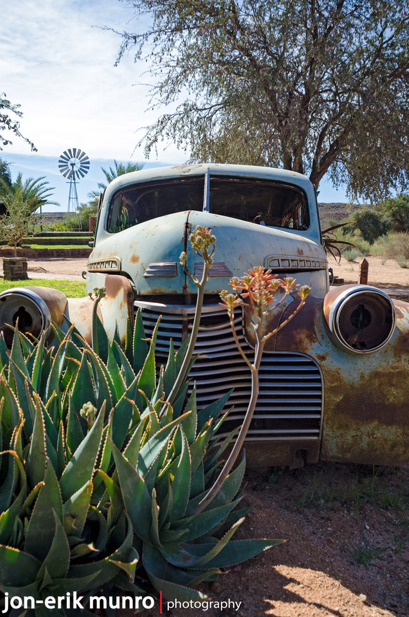 An old American car lies in the bushes at Canyon Road House